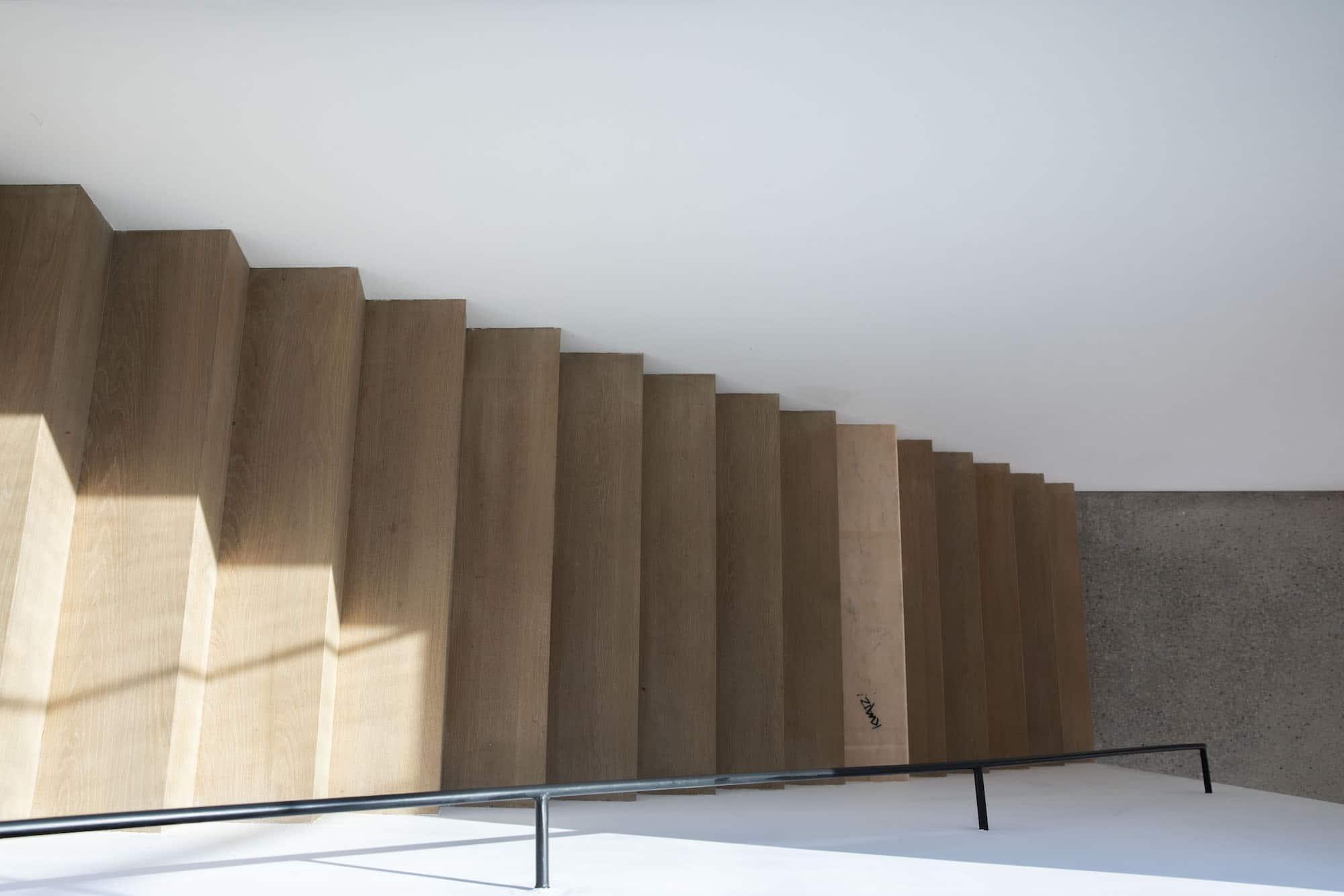Z-trap tussen twee muren in Franse eik (sidenote: de klant heeft één trede door een kunstenaar laten afwerken met een roze natuursteen)