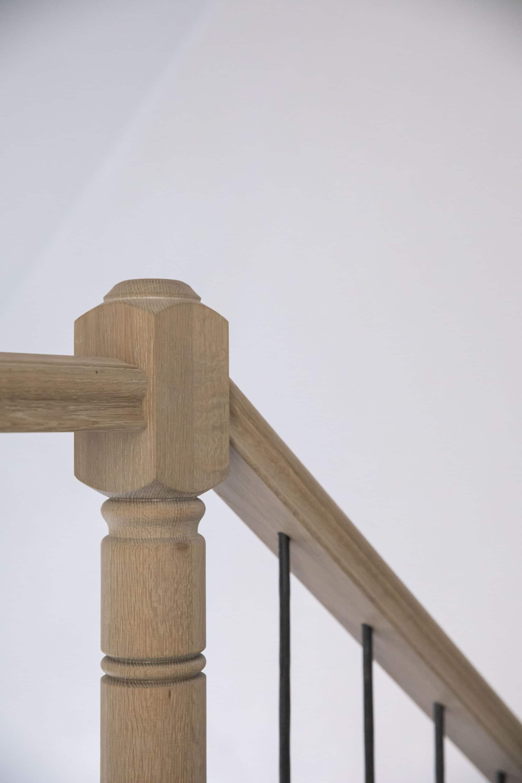 Traditionele gesloten trap in Franse eik met gedraaide beginpaal en smeedijzeren spijlen, met ronde bloktrede