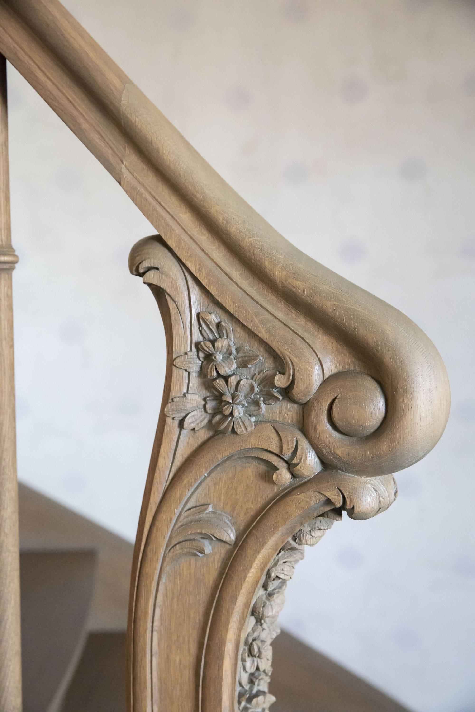 Traditionele gesloten trap in Franse eik met uitgestoken beginpaal en gedraaide balusters, met ronde bloktrede en wrongstuk