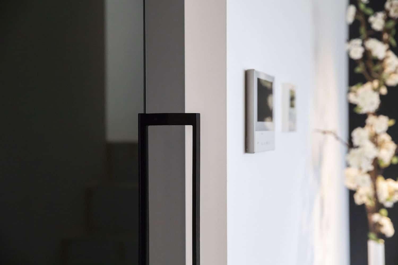 Zwart getinte glazen deur met vloerveersysteem type Dorma